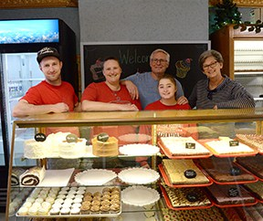 Members of staff at the Betty Kaye bakery, stood behind a counter filled with baked goods
