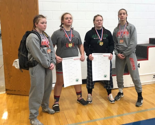 Four girls at state wrestling tournament with awards