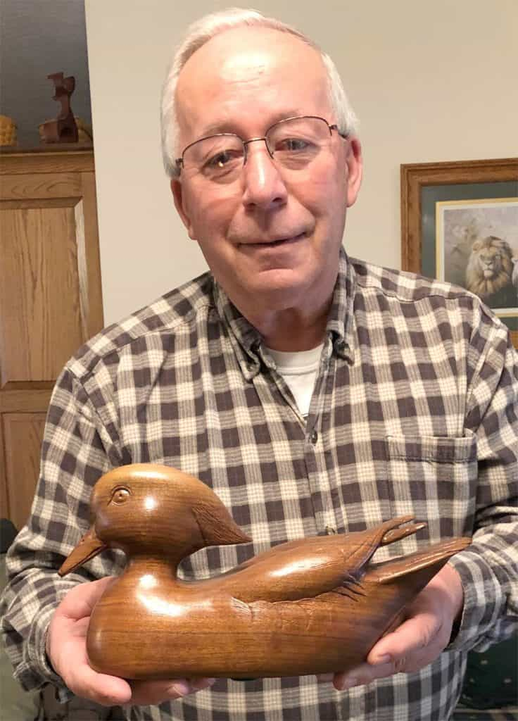 Chuck Huddleston displays a duck he carved from walnut, a piece that required 400 hours to complete.