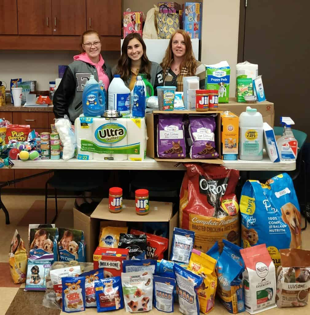 Pictured with the items are (from left): Emily Waggoner and Eva Johnson, members, and high school advisor Sara Cunningham.